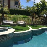 Pool and Spa with Artificial Grass white coping and stack stone on raised bond beam